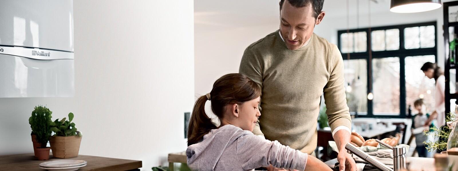 Muž s dcerou v kuchyni před plynovým kotlem